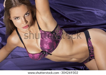 Sexy girl in lingerie posing on the bad - stock photo