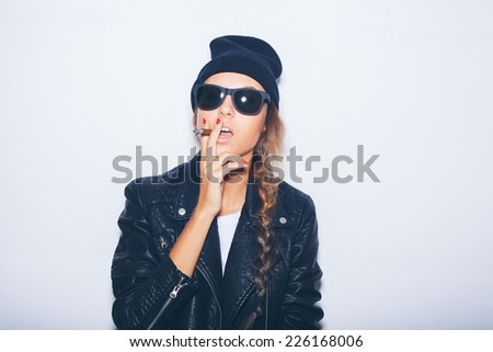 Sexy girl  in sunglasses and black leather jacket smoking cigar.  White background, not isolated - stock photo