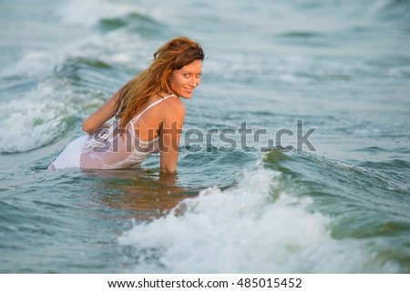 Sexy girl in the ocean waves. fashion portrait of a girl on the sea. beautiful girl in a wet white dress