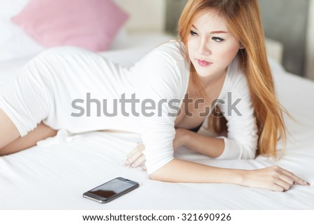 sexy girl in underwear using her mobile phone in bed