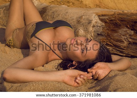 Sexy girl lying on the beach of Crimea in sunset light.