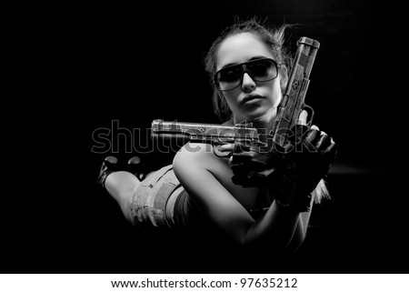 Sexy girl lying on the floor with guns - stock photo