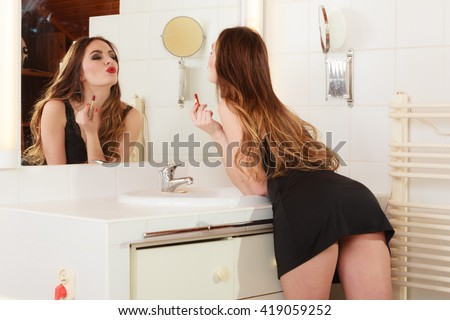 Sexy girl making makeup in bathroom. Woman take care about look. Looking into a mirror. - stock photo
