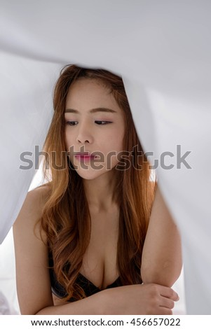 sexy girl poses in white bed sheets - stock photo
