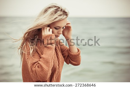 sexy girl poses on a beach. beautiful blonde enjoys walk on the coast - stock photo