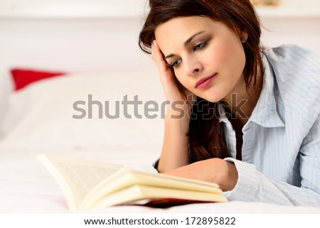 Sexy girl reading a book lying on the bed