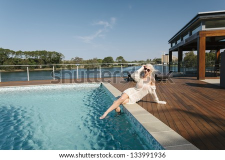 Sexy girl relaxing poolside - stock photo