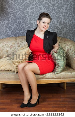 sexy girl wearing red dress sits on a sofa - stock photo