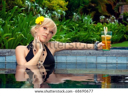 sexy girl with a cocktail in the pool - stock photo