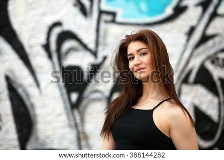 Sexy girl with black top standing in front of a wall with graffiti