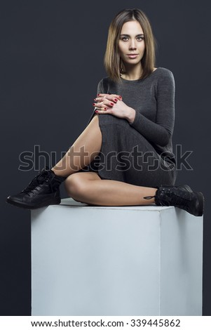sexy girl with brunette hair in grey dress sitting on white cube. Perfect hairdo and skin.  - stock photo