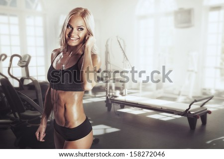Sexy girl with headphones relaxing in the gym - stock photo