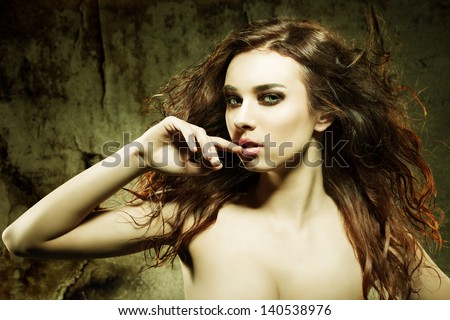 sexy girl with long brown flying hair and elegant make-up looking in camera in sensual pose with fashiion color and grunge background - stock photo