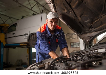 Sexy girl with long legs lying under car checking the engine and auto mechanic standing near her giving her tools at the car repair shop. Girl wearing high heels blue jeans skirt. View from the top. - stock photo
