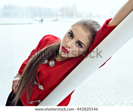 Sexy girl with red lips and black eyes. Young female model portrait wear red blouse black leggings and leather boots. Attractive Fashion lady with long brown hair wear cool outfit and high heels - stock photo