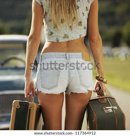 Sexy girl with suitcases, vintage cars in the background - stock photo
