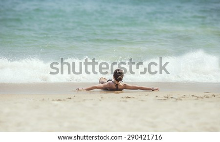 Sexy girli lying on a sandy beach. - stock photo