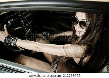 Sexy glamour girl sitting in a sport car - stock photo