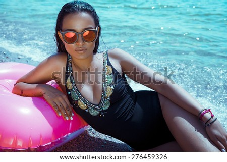sexy glamour model with long wet hair in black swimsuit and sunglasses lying on inflatable circle . Shot on the beach, horizontal