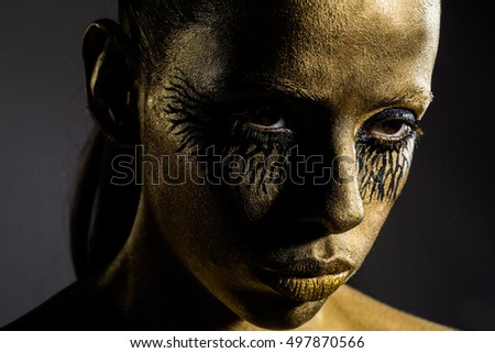 sexy golden woman or girl has pretty face with makeup and body art metallized color and black eyes, closeup
