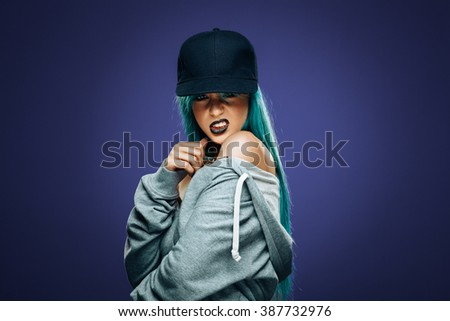 Sexy hip hop woman in hoodie and cap - stock photo