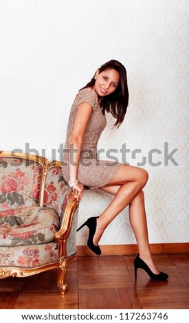 sexy hispanic sitting on sofa - stock photo