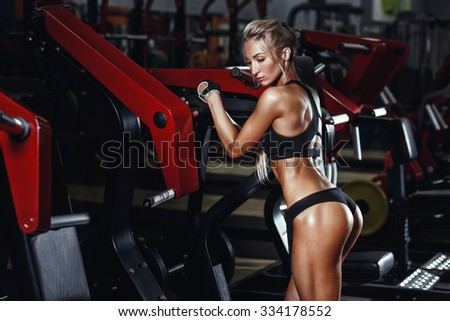 Sexy hot blonde fitness bikini girl with perfect shape body and butt posing and relaxing in gym - stock photo