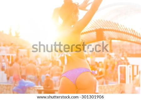 Sexy hot girl wearing brazilian bikini dancing on a beach party event in sunset. Crowd dancing and partying at poolside in background. Summer electronic music festival. Hot summer party vibe. - stock photo