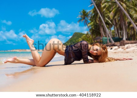 Sexy hot summer portrait of young beautiful smiling happy woman lying on the beach with yellow sand and palms on the sea vacation style  - stock photo