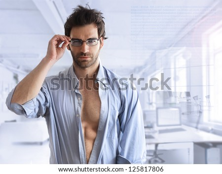 Sexy hunk male model with open shirt in modern business setting with blue toning - stock photo
