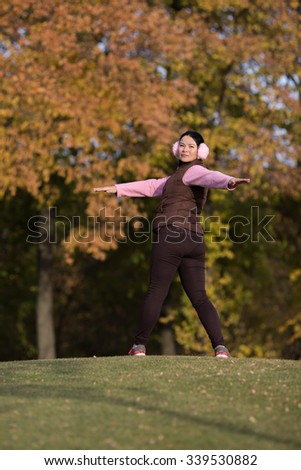 Sexy Korean lady stretching and training in the autumn park. Attractive young woman in sportswear dreaming to be healthy. - stock photo