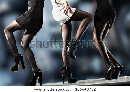 Sexy ladies in short evening dresses wearing tights and high heels dancing on bar counter against abstract blurred background.  - stock photo