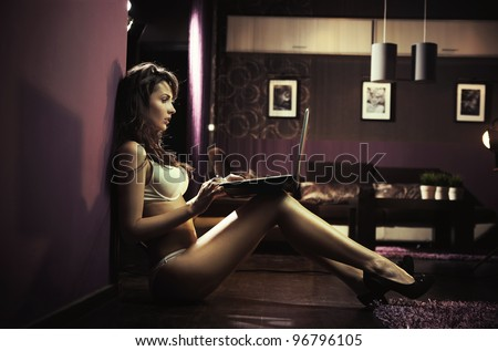 Sexy lady browsing internet late night - stock photo