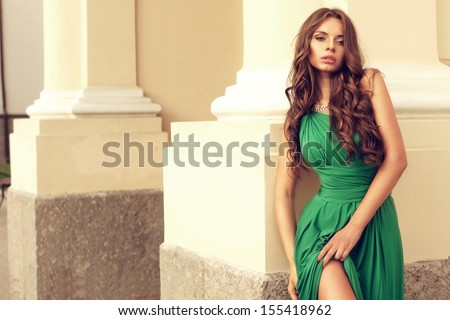 sexy lady in green dress standing near yellow wall at street              - stock photo