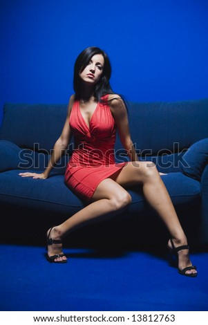 sexy lady in red dress on blue sofa - stock photo