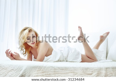 Sexy lady laying and resting on the bed - stock photo