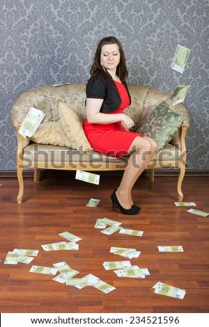 sexy lass sitting under euros rain - stock photo