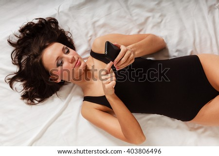 Sexy lazy girl in body underwear lying on bed texting on mobile phone. Woman relaxing lazing in bedroom at the morning. - stock photo