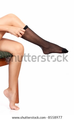 sexy legs of a woman fitting a black stockings - stock photo