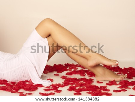 Sexy legs of a woman surrounded with rose petals - stock photo