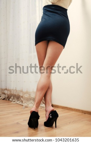 Sexy Legs Of WOman In Short Black Skirt Rear View