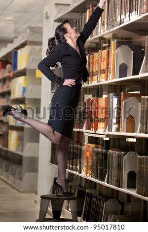 Sexy librarian reaching for a book high on a shelf - stock photo