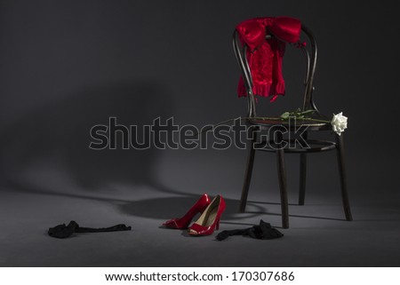 Sexy lingerie, shoes and a white rose on a retro chair. - stock photo