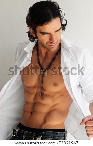 Sexy macho man opening shirt exposing muscular torso and abs against white neutral background