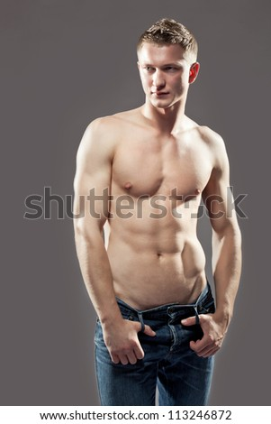 Sexy macho shirtless man with a muscular body posing in jeans with his thumbs hooked in the belt loops