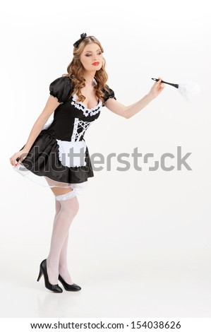 Sexy maid. Beautiful young maid in white pantyhose holding brush and looking away - stock photo
