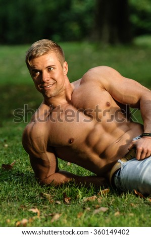 Sexy male model posing without t-shirt in the nature