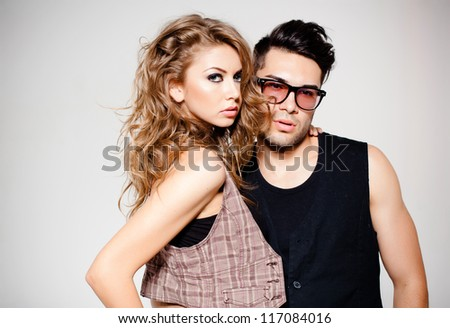 Sexy man and woman dressed casual posing in a studio -  retro colorized photo