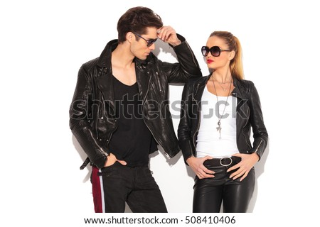 sexy man and woman in leather jackets looking at each other while standing against white wall
