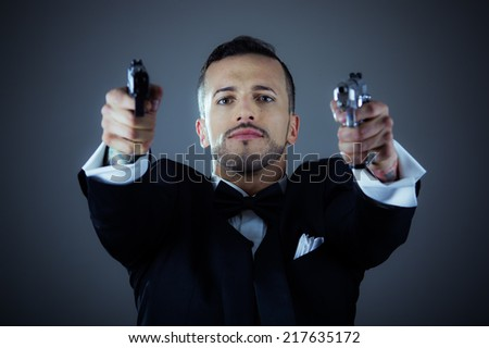 Sexy man gangster agent criminal police in a tuxedo pointing two guns - stock photo